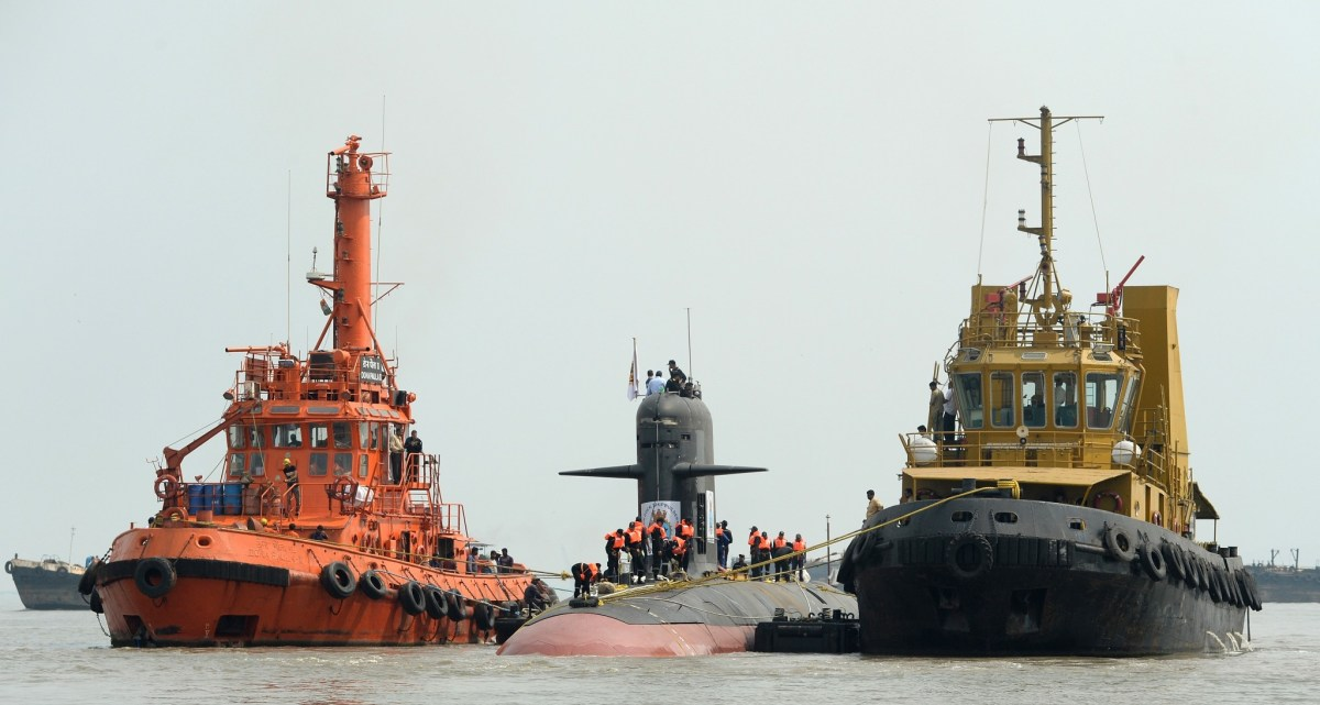 A Scorpene submarine is escorted by tugboats as it cruises into the Naval Dockyard in Mumbai. The first submarine of Project 75 built by Mazagon Dock Shipbuilders Limited was set afloat on October 28, 2015. Photo: AFP/Indranil Mukherjee