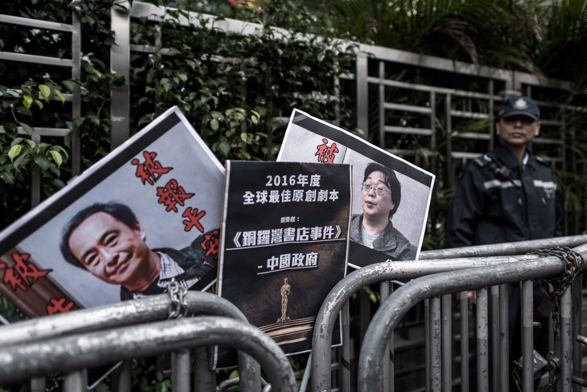 Placards showing two of the abducted booksellers left by protesters outside the China liaison office in Hong Kong in January, 2016. Photo: AFP/ Philippe Lopez
