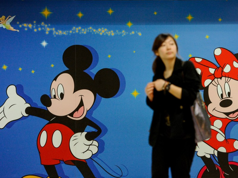 A woman walks past an advert for Hong Kong Disneyland. Photo: AFP / Philippe Lopez