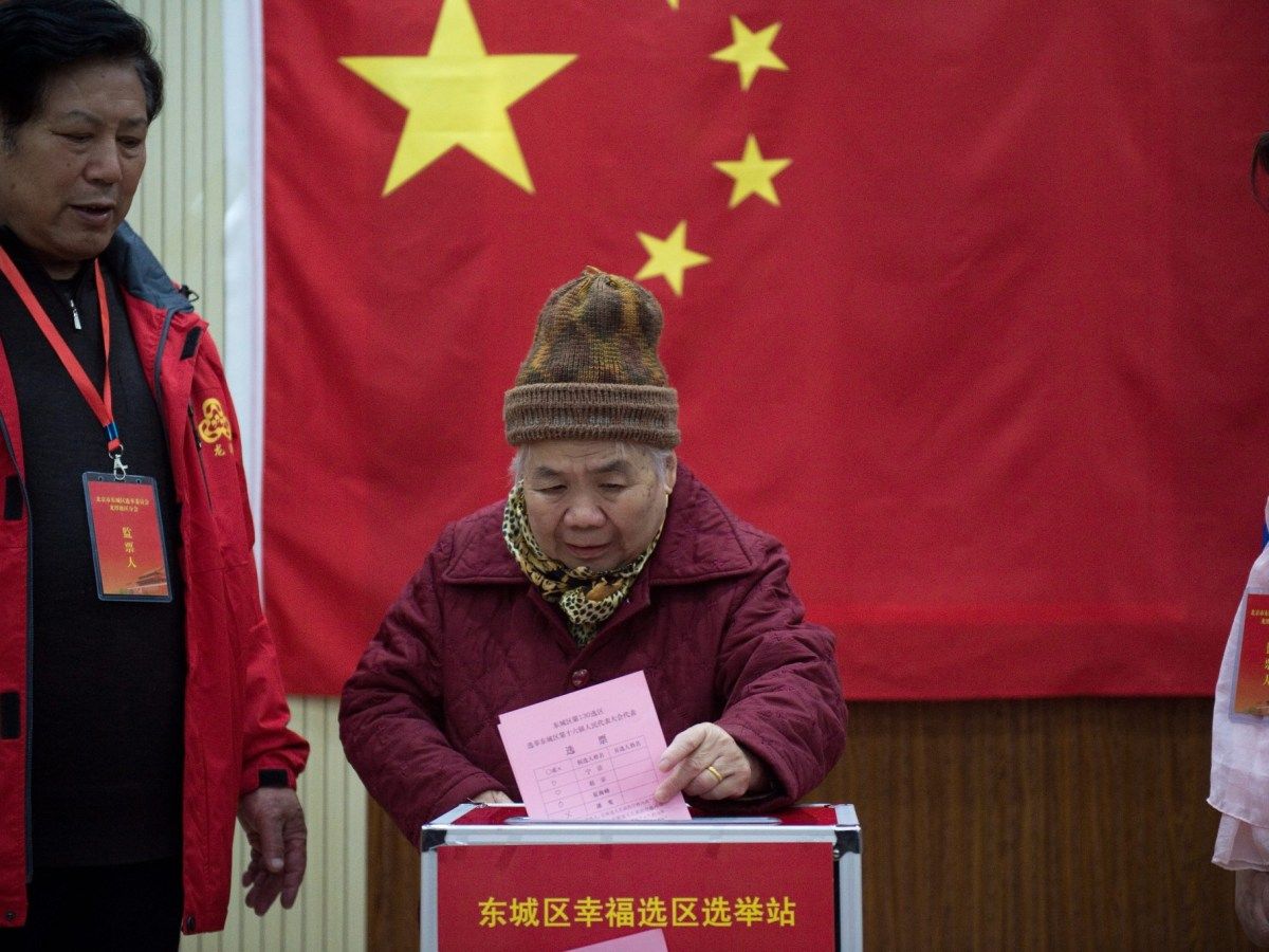 An elderly woman casts her vote at a polling station in Beijing during nationwide local legislature elections on November 15. Photo: AFP/Nicolas Asfouri