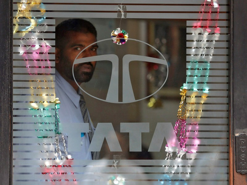 A private security guard looks out from a glass door of a Tata Mutual Fund office building in Mumbai. Photo: REUTERS/Shailesh Andrade