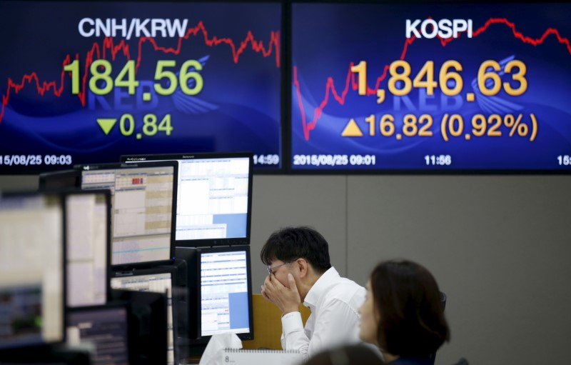 A currency dealer works in front of electronic boards showing the Korea Composite Stock Price Index (KOSPI) (R), and the exchange rates between the Chinese yuan and South Korean won (L), at a dealing room of a bank in Seoul, South Korea, August 25, 2015. Photo: Reuters/Kim Hong-ji