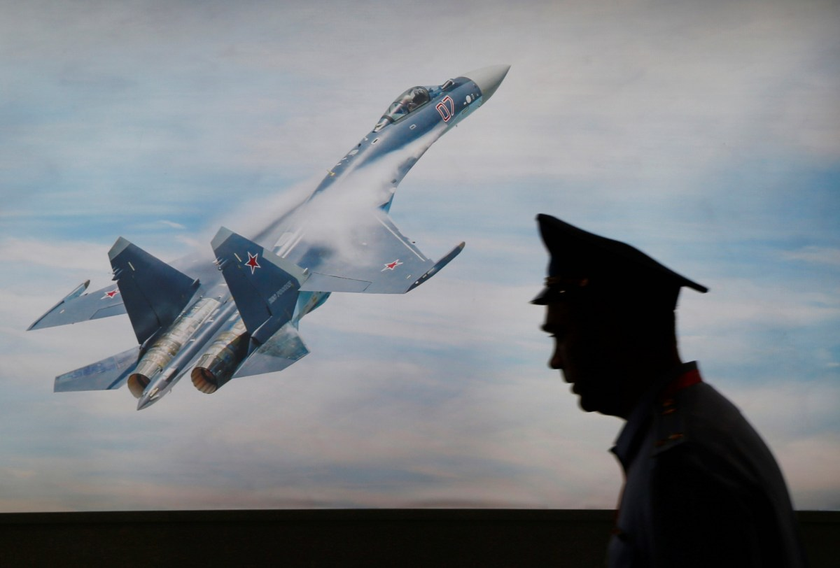 A military personnel member walks past a picture of a Sukhoi jet fighter during the Indo Defence Expo in Jakarta, Indonesia, on November 2, 2016. Photo: Reuters / Beawiharta