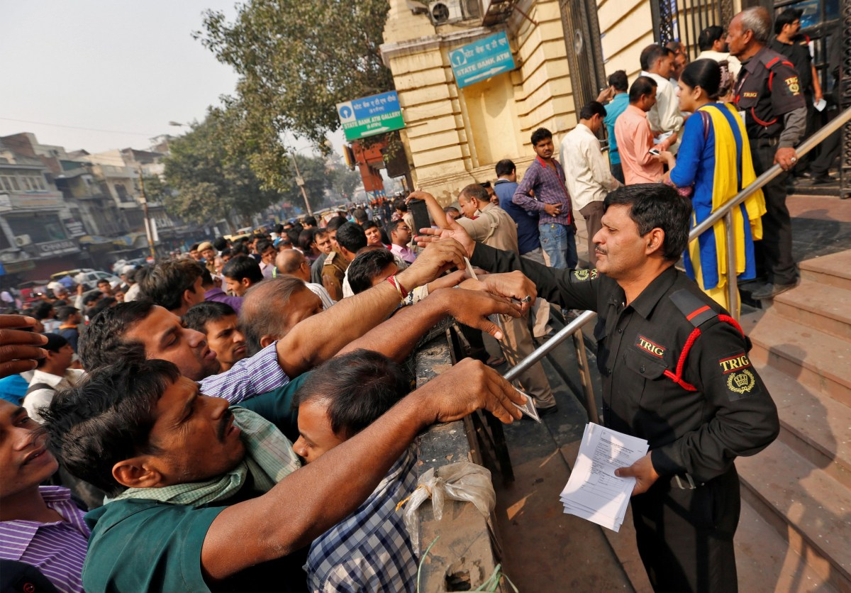 A security guard hands out request slips for the exchange of old high denomination bank notes at a branch of the State Bank of india in Old Delhi, India, November 10, 2016. Photo: Reuters/Cathal McNaughton