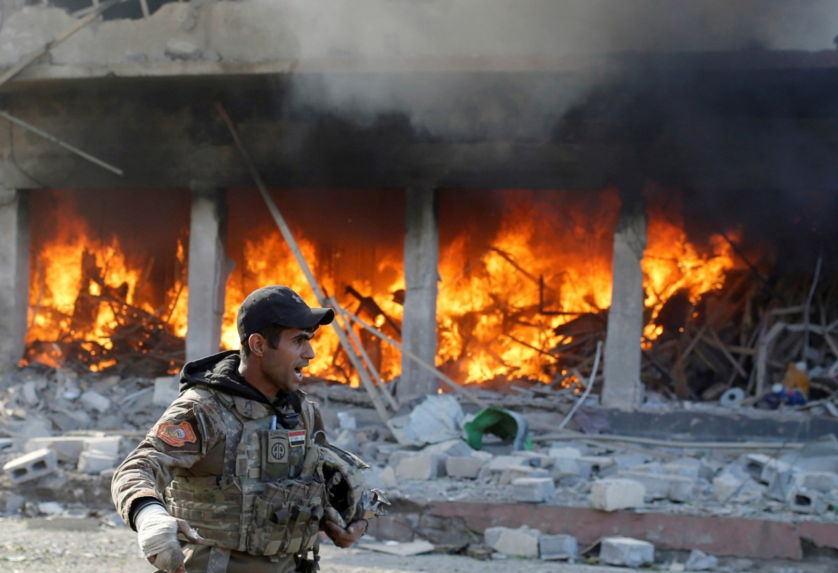An Iraqi special forces soldier shouts in front of a burning house after an Islamic State suicide car bomb attack against Iraqi special forces during clashes in Mosul, Iraq, November 19, 2016. Photo: Reuters/Goran Tomasevic