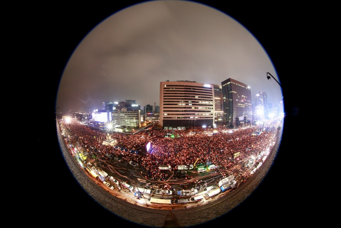 An image taken with a fish-eye lens shows South Koreans in a candlelight procession marching toward the presidential house during a rally against President Park Geun-Hye on a main street in Seoul, South Korea, 26 November 2016. Photo:  Reuters/Jeon Heon-kyun