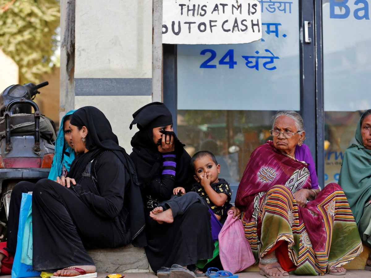 Women sit outside a bank in Ahmedabad, India, November 29, 2016. Photo: Reuters/Amit Dave