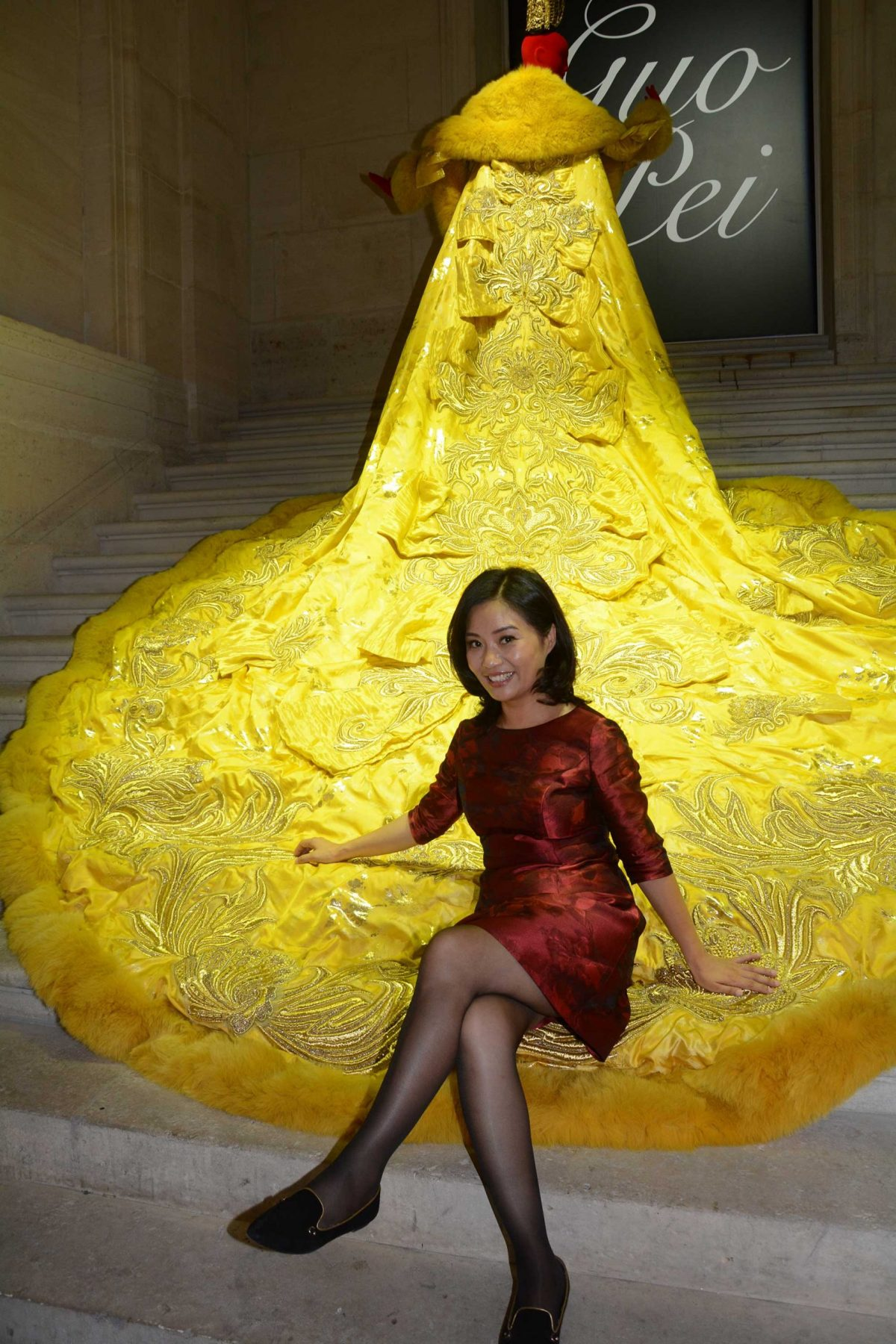 Guo Pei poses with the canary yellow gown shje designed for Rihanna to wear at 2015's Met Ball. Photo courtesy of Guo Pei