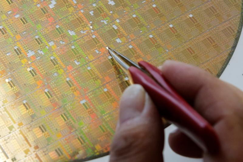 A researcher takes a piece from a semiconductor wafer. Photo: Reuters, Kim Kyung-hoon