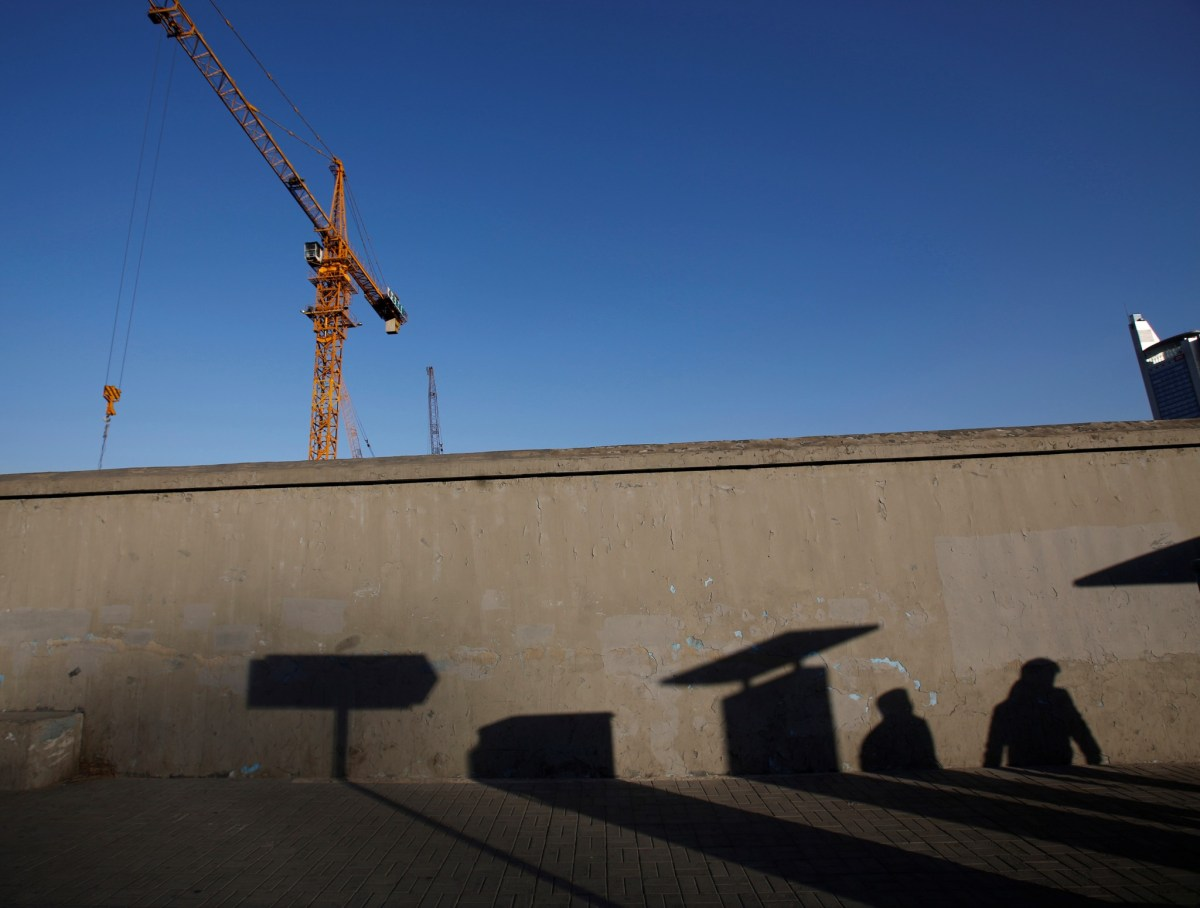 Pedestrians cast their shadows on a wall next to a construction site in Beijing. Photo: Reuters/Kim Kyung-Hoon