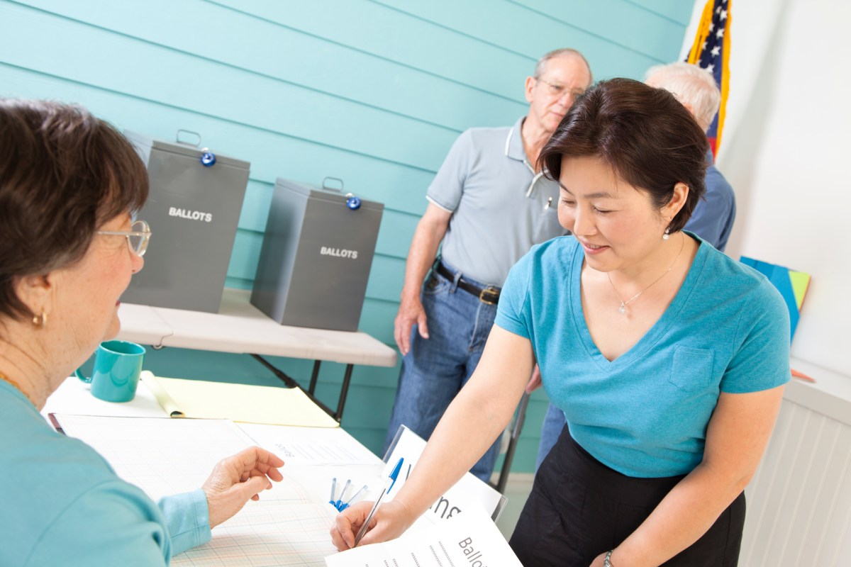 Multi-ethnic, mixed age group of people registering and voting in the November elections at their local polling station. Photo: iStock/Getty Images