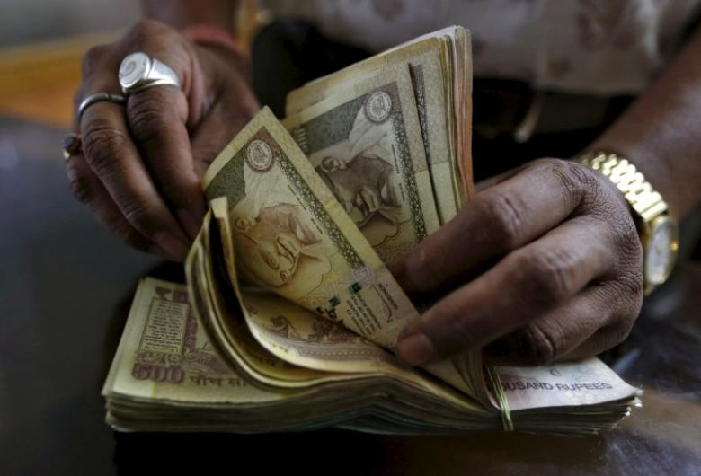 A money lender counts Indian rupee currency notes at his shop in Ahmedabad. Photo: Reuters/Amit Dave