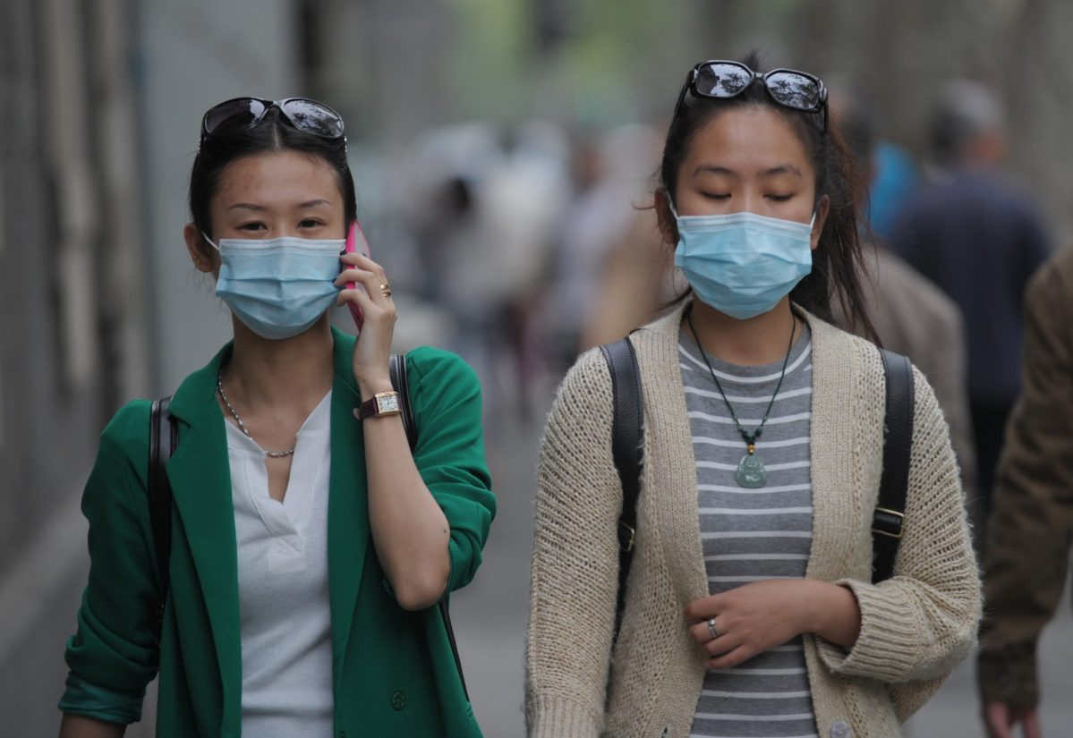 Women wear face masks on a street in Shanghai on April 16, 2013 as China's H7N9 bird flu virus spreads further afield. In total nationwide 62 people have been infected and 14 have died of the disease since Chinese authorities announced two weeks ago they had found H7N9 in humans for the first time. Photo: AFP/Peter Parks