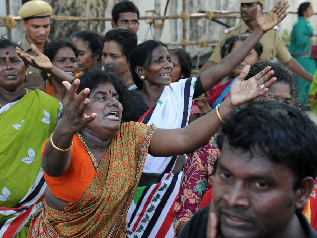 Indian supporters of Tamil Nadu Chief Minister Jayalalithaa Jayaram react as they wait to catch a glimpse of her funeral procession in Chennai on December 6, 2016. Photo: AFP / MANJUNATH KIRAN