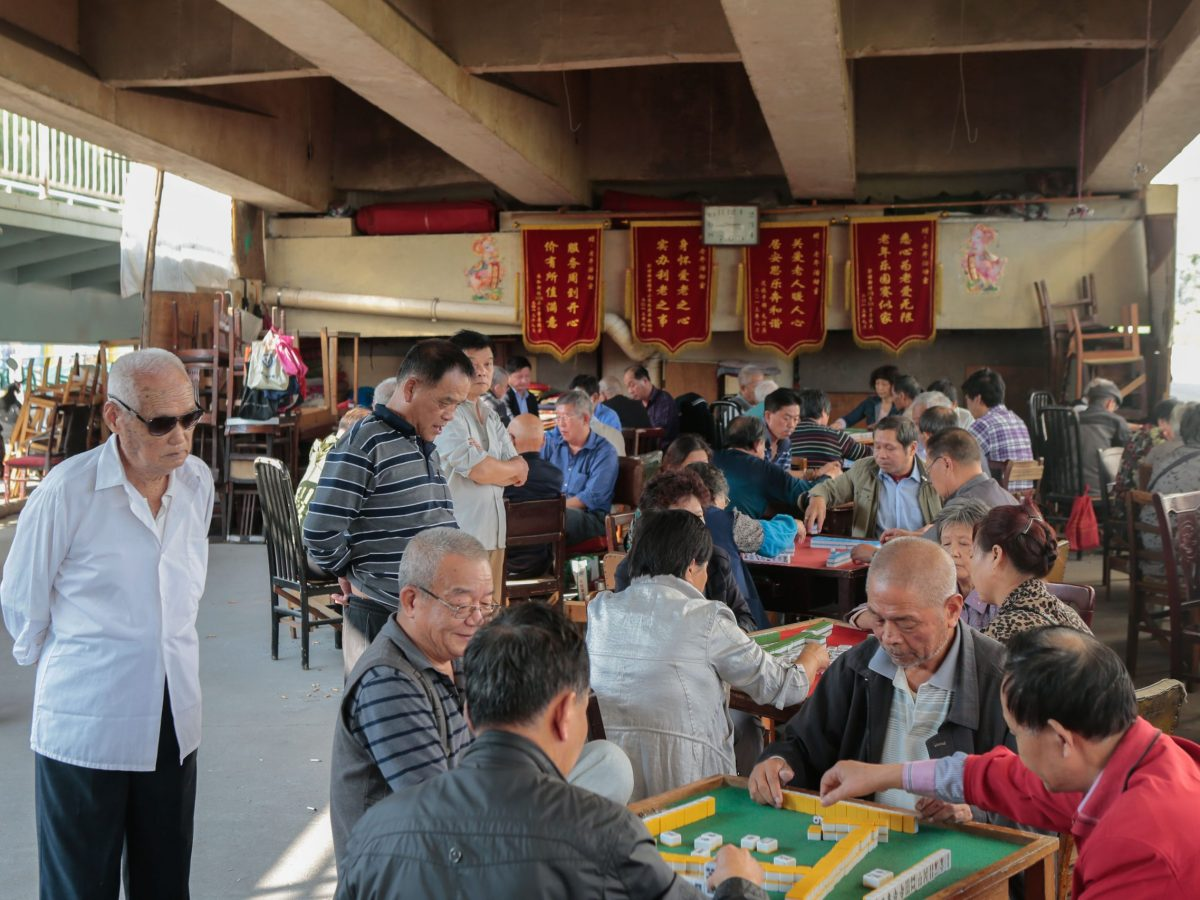 Elderly Chinese people play mahjong under an elevated highway in Shanghai. Photo: AFP