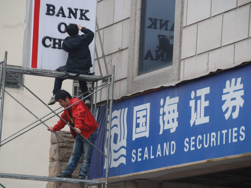 Chinese workers install a signboard of Bank of China next to a branch of Sealand Securities in Hechi city, south China's Guangxi Zhuang Autonomous Region. Photo: AFP