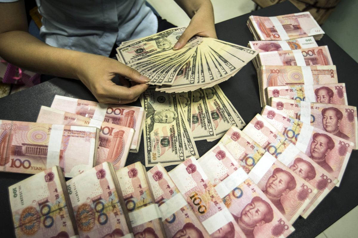 A Chinese clerk counts US dollar banknotes next to yuan bills. Photo: AFP/Xu Jingbai/Imaginechina