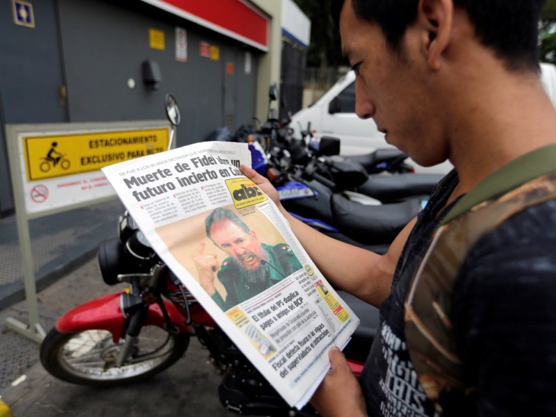 A worker reads a local newspaper with an image of Cuban revolutionary leader Fidel Castro, after the announcement of Castro's death, in Asuncion, Paraguay, November 27, 2016. Photo: REUTERS/Jorge Adorno