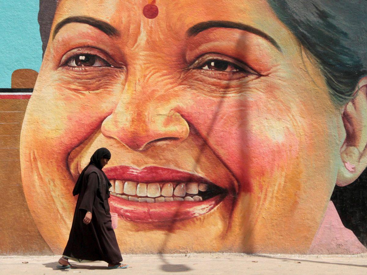 A woman walks past a portrait of Jayalalithaa Jayaraman in Chennai. Photo: Reuters/Babu