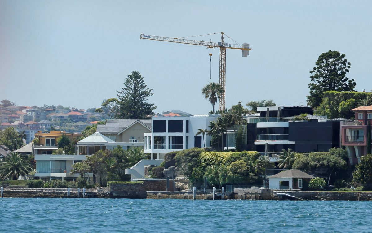 A construction tower appears over waterfront property on Sydney Harbour in Australia, December 13, 2016. Photo: Jason Reed