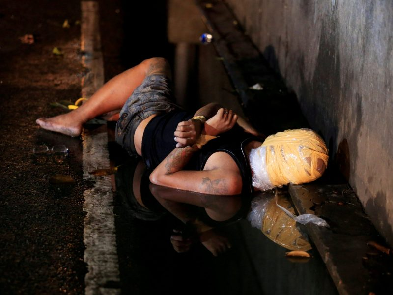 The body of a dead man with his head wrapped in masking tape, whom police said was a victim of a drug-related vigilante execution, lays on a street in Pasay city, metro Manila. Photo: Reuters/Romeo Ranoco