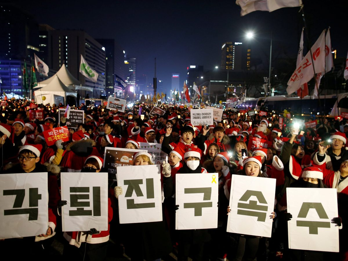 """People dressed in Santa's costumes attend a protest demanding South Korean President Park Geun-hye's resignation in Seoul, South Korea, December 24, 2016. The banner reads """"Resign immediately, Arrest investigation"""".  Photo: Reuters/Kim Hong-Ji"""