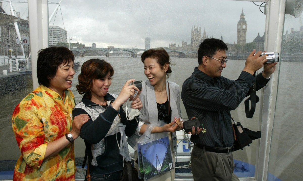 Mainland Chinese tourists take pictures during a cruise on the River Thames, central London. Photo: Reuters/Paul Hacket