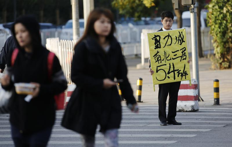 A real estate agent holds a board advertising an apartment for sale, on a street in Beijing. Photo:      Reuters/Kim Kyung-Hoon