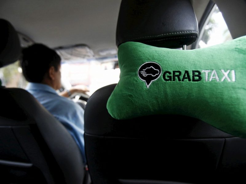 A GrabTaxi logo is seen on a car neck pillow in a taxi in Hanoi, Vietnam. Photo: REUTERS/ Kham
