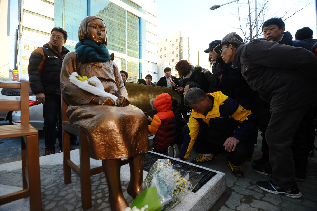 Flowers are laid on a statue of a girl that represents the wartime sexual victims by the Japanese military, during a rally in front of the Japanese Consulate in Busan, South Korea, on December 30, 2016. Photo: Yeo Joo-yeon / News1 via Reuters