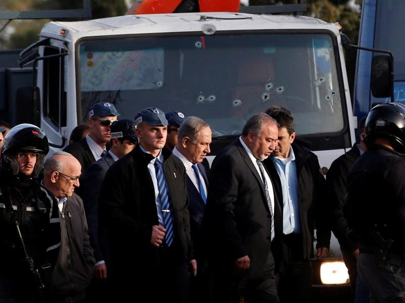 رئيس الوزراء الإسرائيلي بنيامين نتنياهو (وسط) ووزير الدفاع أفيجادور ليبرمان في زيارة للموقع الذي دهس فيه فلسطيني مجموعة من الجنود الإسرائيليين في بداية 2017. صورة: Reuters / Ronen Zvulun