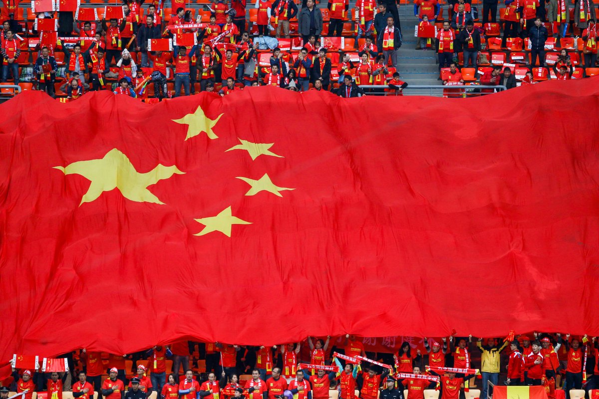 Soccer fans holding a Chinese national flag at a match. Photo: China Stringer Network.