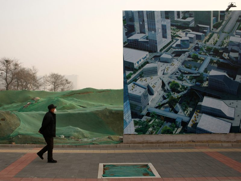 A man walks past an advertising billboard of a commercial property development in Beijing, China, December 31, 2016. Photo: REUTERS/Thomas Peter