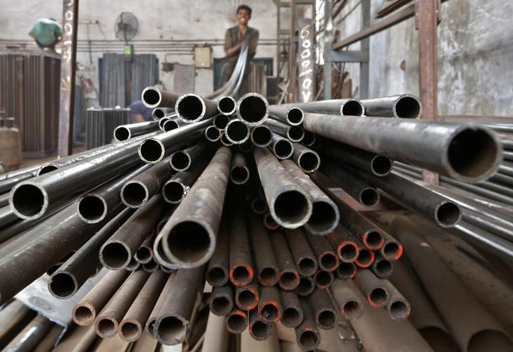 A worker stacks steel pipes in the western Indian city of Ahmedabad.  Photo: Reuters/Amit Dave