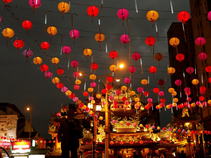 A tourist walks under the lanterns along a street ahead of the Lunar New Year outside Raohe street Night Market in Taipei, Taiwan. Photo: Reuters/Tyrone Siu