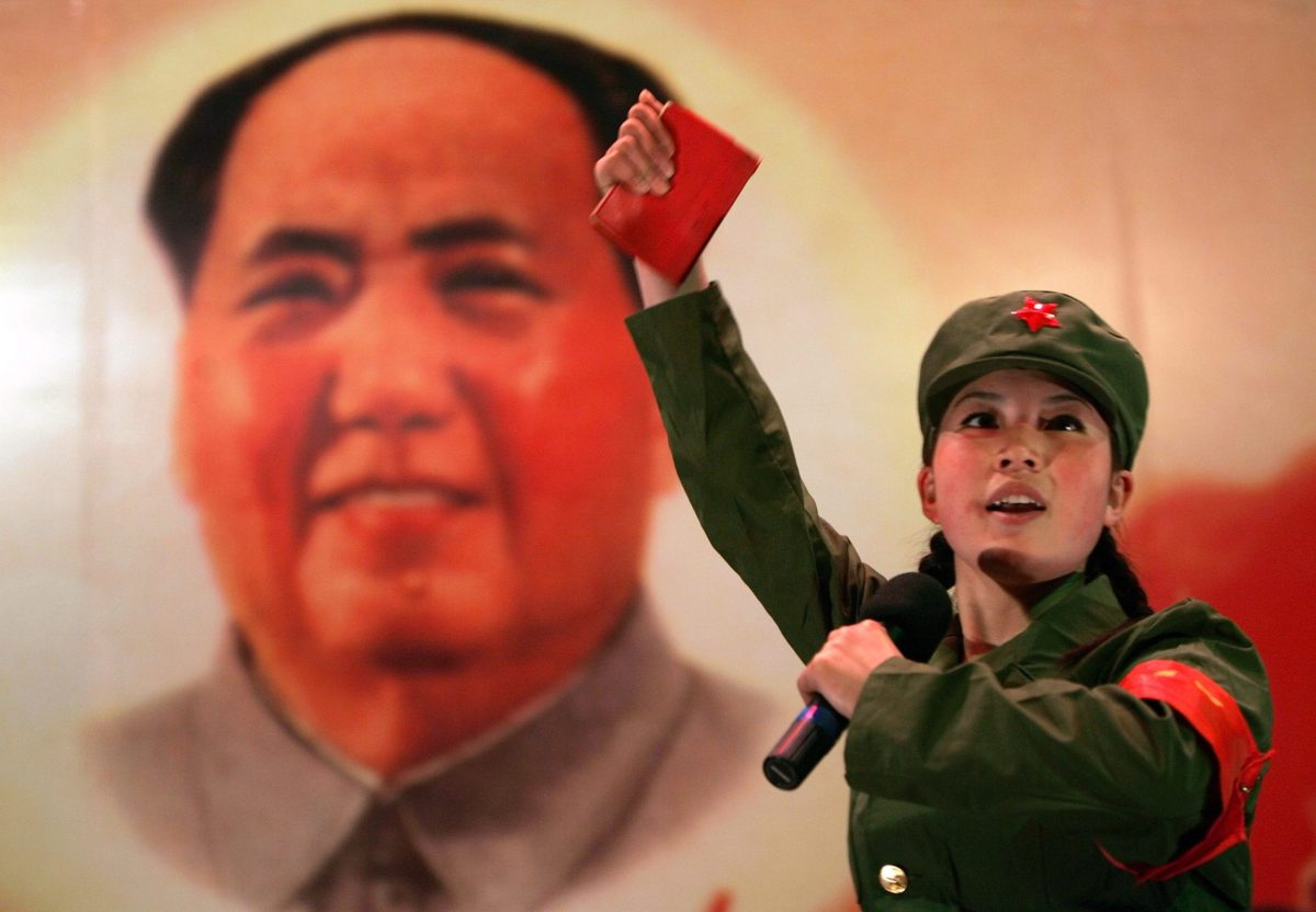 "A Chinese, dressed as a Red Guard and holding a ""Little Red Book"" (quotations of Chairman Mao), performs in front of a portrait of the late Chairman Mao Zedong at a restaurant named ""Red Classic"" in Beijing April 7, 2006. ""Red Classic"" is a theme restaurant based on the Chinese Cultural Revolution which happened between 1966 to 1976. The restaurant is decorated with posters from the period while customers, served by waiters and waitress dressed as Red Guards, enjoy revolutionary songs and dance performances.  REUTERS/Jason Lee - RTR1CBD4"
