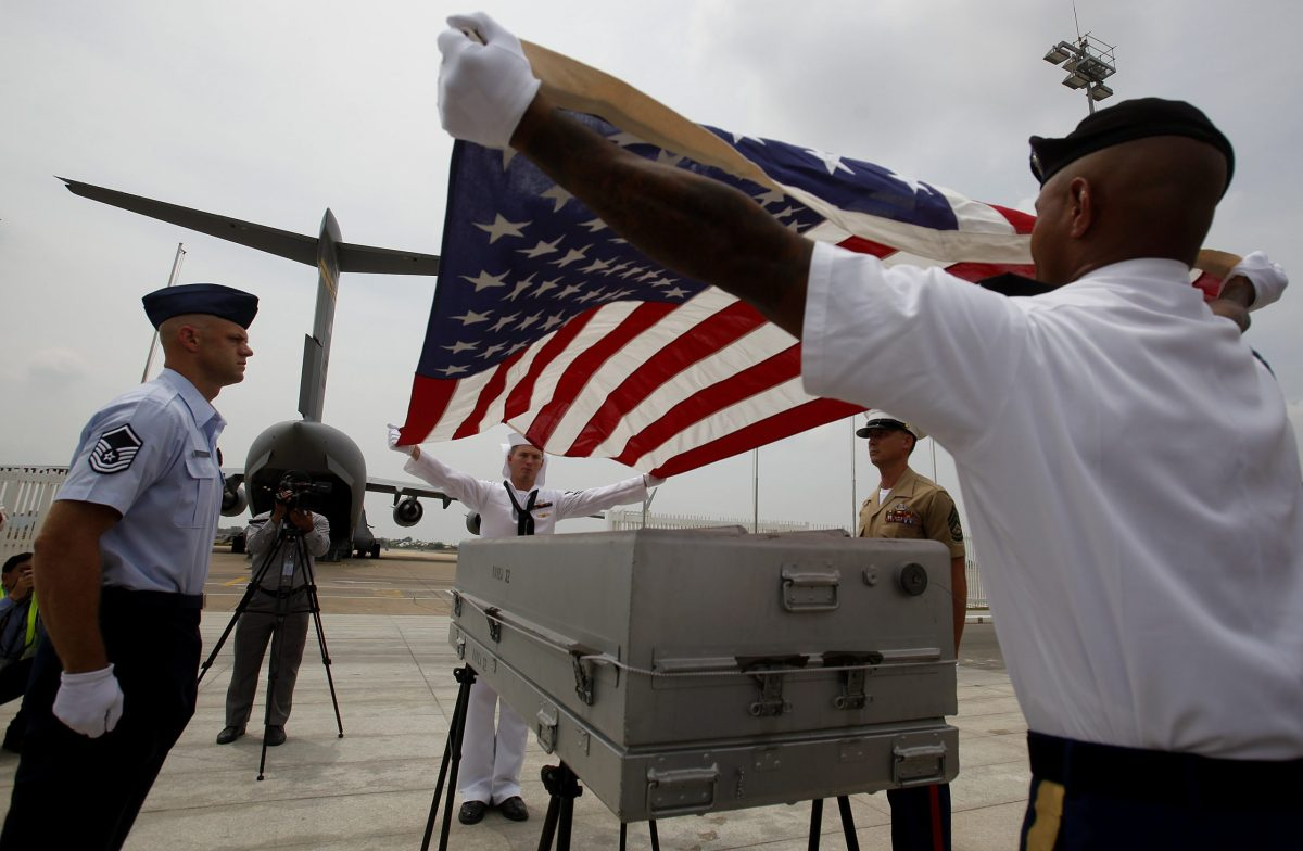 United States personnel prepare a coffin at the Phnom Penh International Airport during a repatriation ceremony on April 2, 2014. Remains believed to belong to missing US military service members found in Cambodia's Kampong Cham province were repatriated back to the US in a ceremony. The US Embassy said that ninety American soldiers were originally missing in Cambodia from the Vietnam Conflict, thirty-seven individuals have been recovered and identified, while 53 remain missing. Photo: Reuters / Samrang Pring