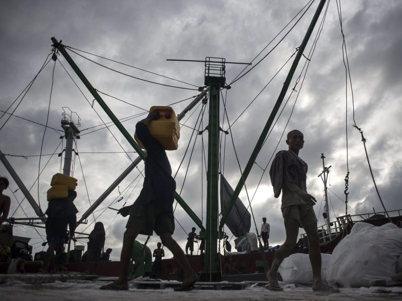 Myanmar workers load containers of oil onto a ship at the Yangon jetty on May 31, 2016. Photo: AFP/Ye Aung Thu