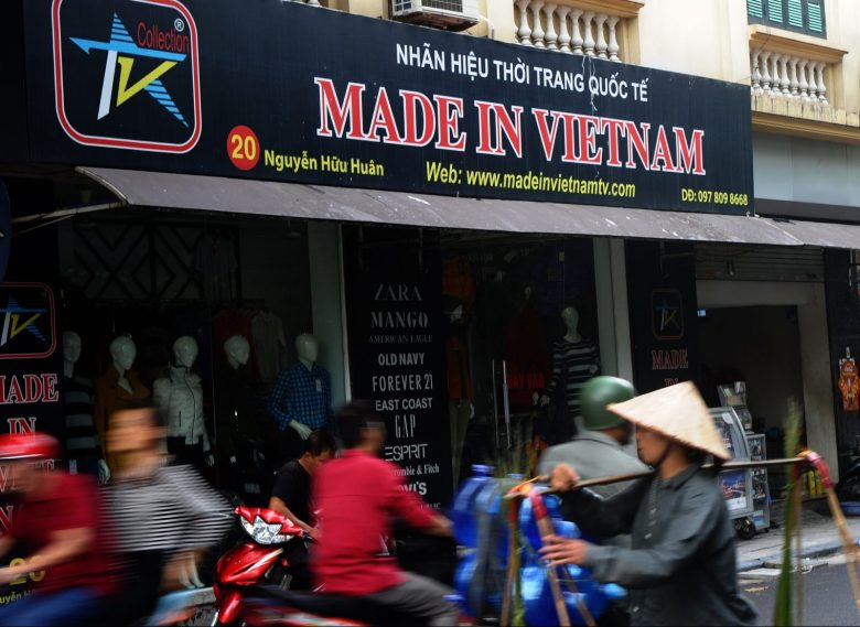 People move past a clothing boutique selling locally made products in downtown Hanoi on October 29, 2014. A EU-Vietnam Free Trade Agreement promises to boost Vietnamese exports and growth. AFP / Hoang Dinh Nam