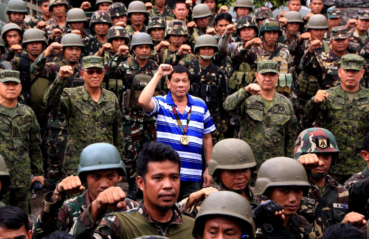 Philippine President Rodrigo Duterte (C) raises a clenched fist with military top brass as he visits troops in Nanagun, Lombayanague in Lanao del Sur in Mindanao island on November 30, 2016. Photo: AFP / Richel Umel