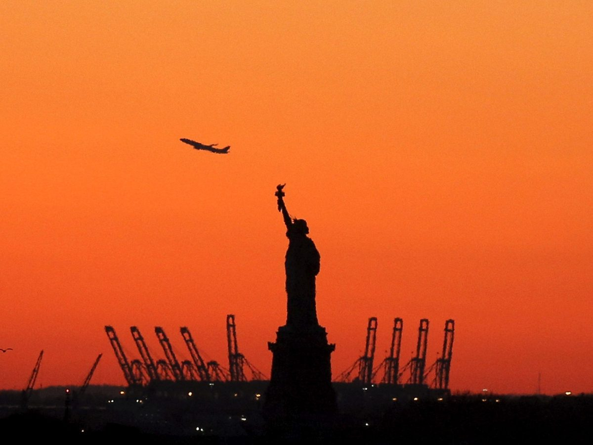 A plane takes off in New Jersey behind the Statue of Liberty in New York's Harbor as seen from the Brooklyn borough of New York February 20, 2016. Photo: Reuters/Brendan McDermid/File Photo