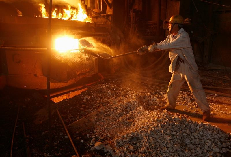 A labourer shovels iron ore into a steel ladle at Wuhan Iron and Steel Group. Photo: Reuters/Stringer