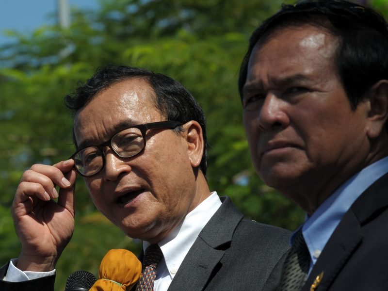 Cambodia National Rescue Party (CNRP) ex-leader Sam Rainsy (2nd R) speaks to people as its now jailed presiden Kem Sokha (R), listens in front of the National Assembly building during a rally to mark Human Rights day in Phnom Penh on December 10, 2014. Photo: AFP/ Tang Chhin Sothy