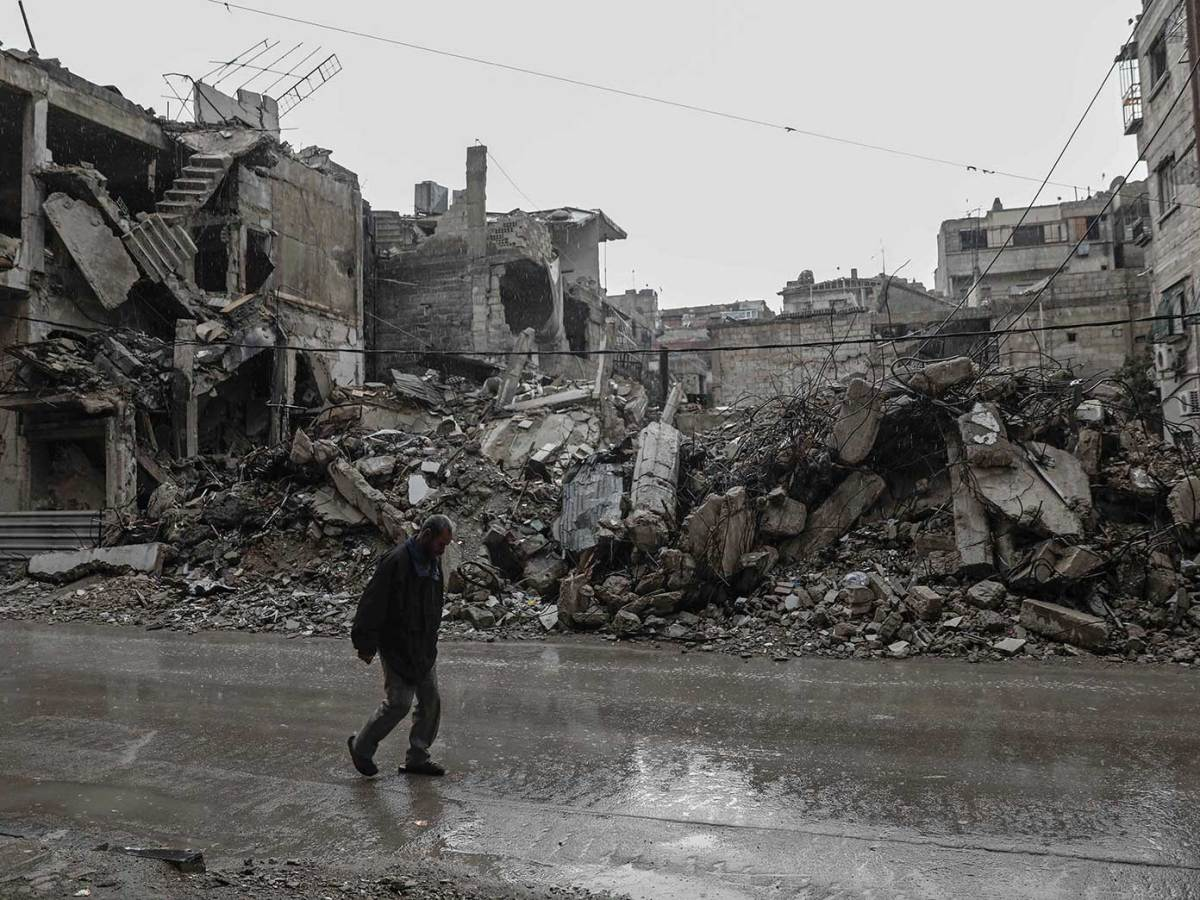 A Syrian man walks past destroyed buildings in the rebel-held town of Douma, on the eastern outskirts of Damascus. Photo: Sameer Al-Doumy, AFP