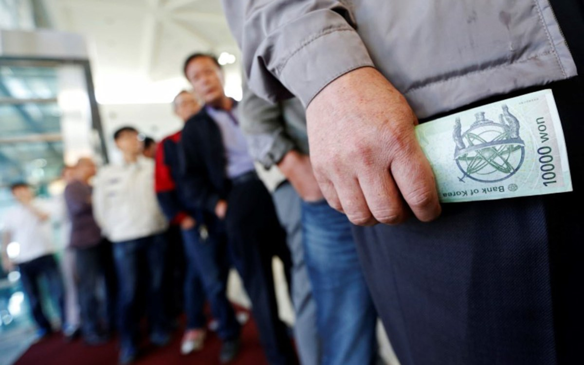 South Korean workers stand in a line to exchange won to US dollar. Photo: Reuters, Lee Jae-Won