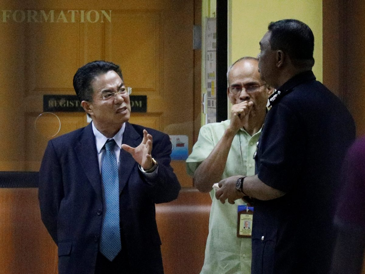 A North Korea official speaks with police at the morgue at Kuala Lumpur General Hospital. Photo: Reuters
