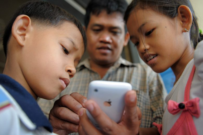 A Cambodian man uses the touch screen of his mobile phone as his children look on in Phnom Penh on May 8, 2010. AFP PHOTO/TANG CHHIN SOTHY / AFP PHOTO / TANG CHHIN SOTHY