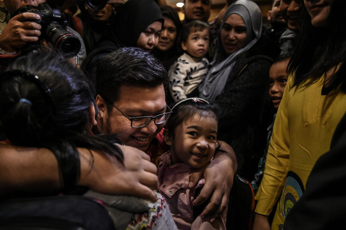 A family member hugs daughters of Mohd Nur Azrin Md Zin, Annur Zhafirah, 5, (right) and Annur Zulaikha, 6, (left) at Kuala Lumpur International Airport. Photo: AFP/Mohd Rasfan