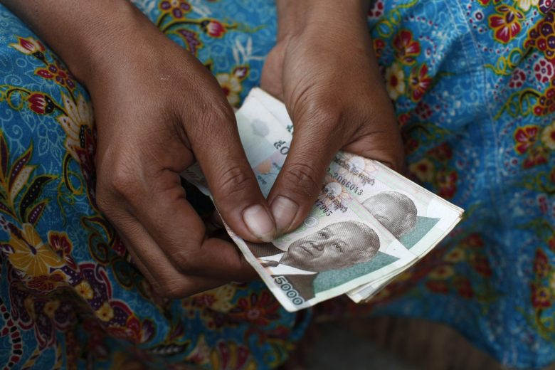 A microfinance customer in Cambodia holds a loan denominated in the local currency, the riel. Photononstop via AFP / Philippe Lissac