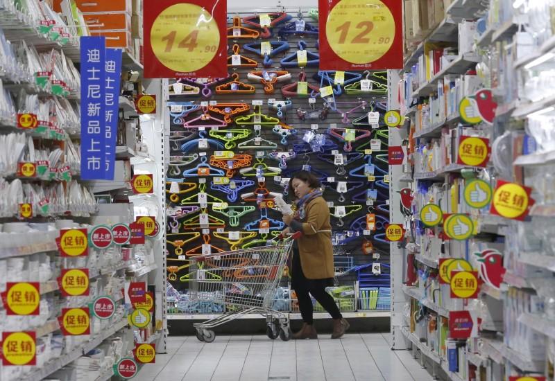 A customer pushes a shopping cart at Sun Art Retail Group's Auchan hypermarket store in Beijing, China, November 9, 2015. REUTERS/Kim Kyung-Hoon